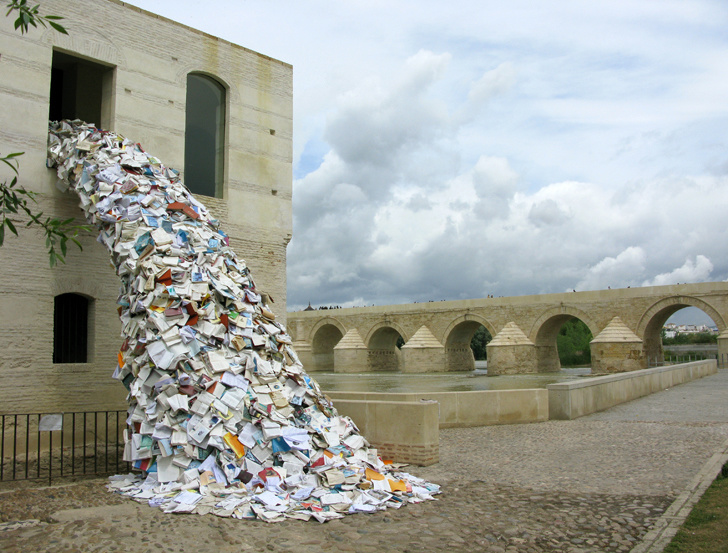 Thousands of paperback books falling out of a window.